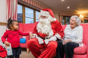 Two year old girl with Santa and care home resident