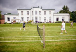 Two tennis players on the grass court in fron of Barrowhill Hall care and nursing home