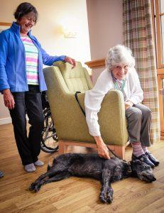 Two women enjoying a dog's company