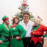 Elvis impersonator standing with three ladies dressed as elves