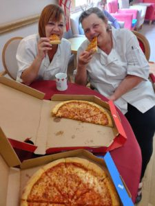 Two staff at Barrowhill Hall enjoying pizzas donated by a local takeaway